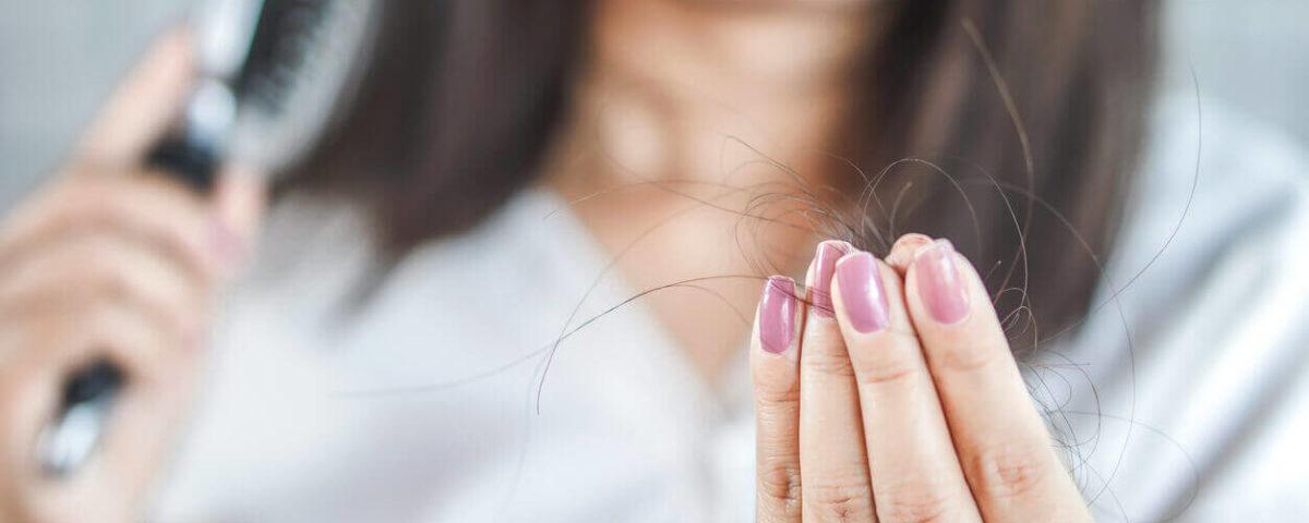 mulher percebe a queda de cabelo ao observar fios capilares nas mãos