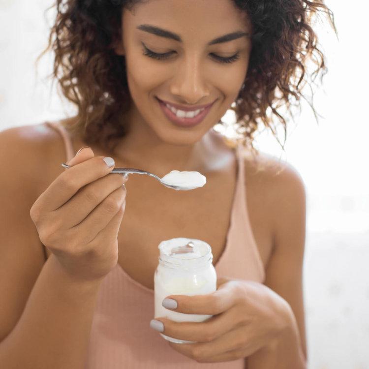 mulher come iogurte com probióticos