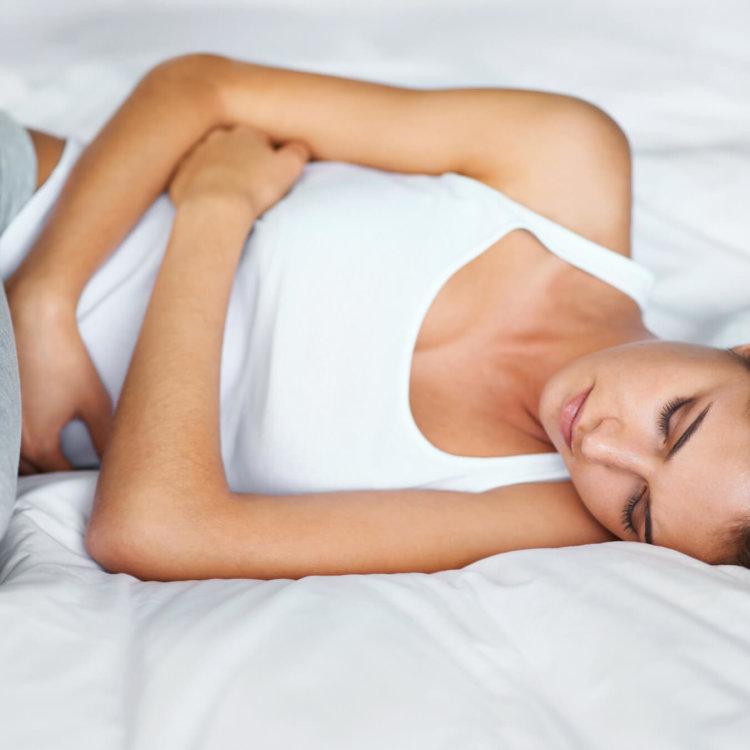 mulher deitada na cama, com síndrome do ovário policistico
