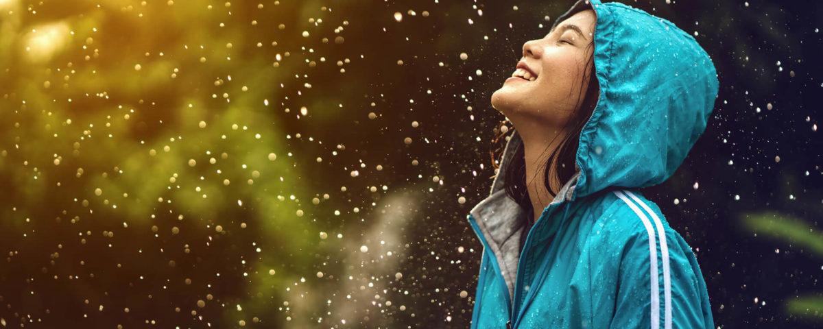 Mulher asiática, vestindo uma capa de chuva, ao ar livre. Ela está feliz