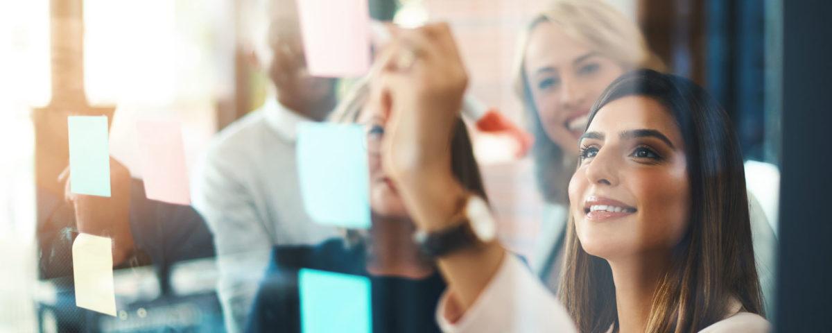 Mulher colando post it no vidro como exercício para melhorar a memória