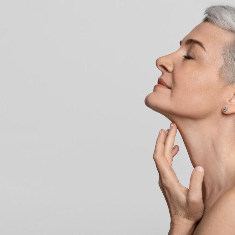 Mulher madura, de perfil, toca delicadamente sua pele na região do pescoço e faz referência aos benefícios dos injetáveis na estética.